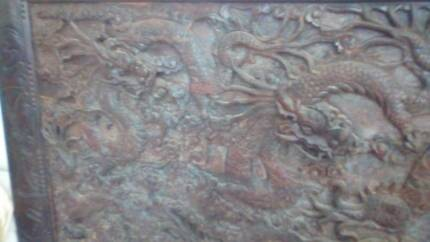 Chinese wood carving of dragons chasing peal.