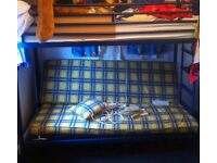 Bunk bed. Blue tubular metal. Upper single, bottom couch folds down to small double bed.
