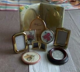 Nine different small picture frames. Some are gold plated, some plastic, some material.