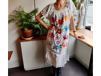 Maxi white dress with folk themed embroidery pattern.