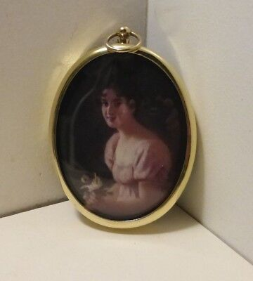 Miniature of pretty dark haired girl in pink set in an oval brass frame