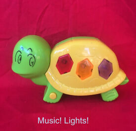 Musical, flashing lights tortoise toy. Plays 3 tunes. Batteries included. Happy to post.