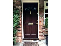 Hardwood pannelled solid front door with brass furniture