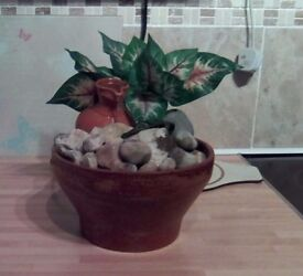 Indoor water fountain of a rust coloured bowl containing a jug, leaves, rocks, pebbles. Working.