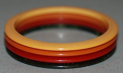 BAKELITE THIN BANGLES OR SPACERS GROUP OF FOUR IN RED, BLACK, ORANGE AND YELLOW