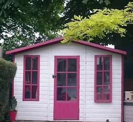 Beautiful 10 x 6 summer house painted in white with berry red trims.