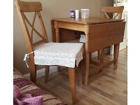 Ikea extendable dining table with two chairs and cushions