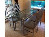 Glass topped dining table and four chairs