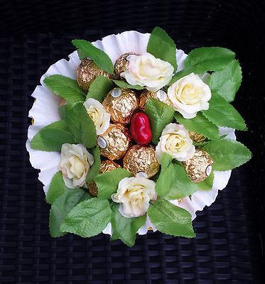 Mit ein paar Blumen angereichert wird der Pralinenstrauß zum schönen Blickfang. (© xyx_15)