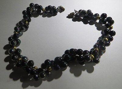Collier ras du cou composé de nombreuses perles synthétiques irisées et plaquées