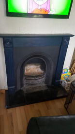 Cast Iron inset fireplace with wooden surround and granite hearth