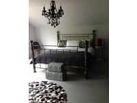 Super King bed in large room in interior designed house overlooking garden.