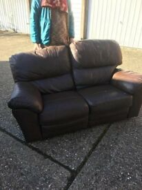 Brown two seater reclining sofa.