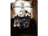 Various cricket equipment including footwear
