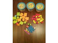 Three Play Doh buckets with plastic pieces