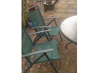 Circular glass topped garden table and six chairs