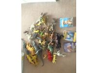 Large amount of plastic dinosaurs with dinosaur books and dvds