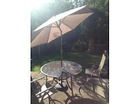Garden furniture set with table, 4 chairs, and parasol.