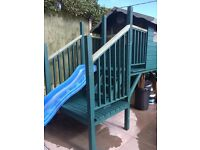 raised wooden playhouse with wavy slide