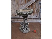Large stone bird bath - boy and girl playing hide and seek .