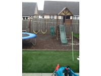 wooden climbing frame with swings slide and picnic bench