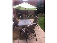 Quality large glass patio table, 4 folding reclining chairs & parasol