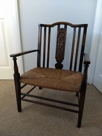 Antique Arts and Crafts rush seat armchair with carved back panel.