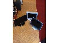 2 computer monitors and flatscreen TV
