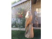 Chainsaw carving tree stump owl. Garden sculpture wood carving