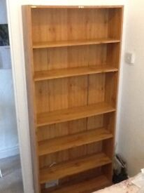 A brown bookcase with five adjustable shelves