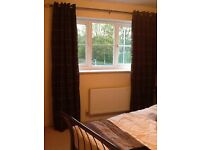 Fully lined full length dark brown curtains with an orange and light brown pattern