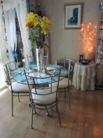 Glass table & cream cushioned chairs