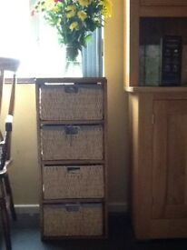 Wooden unit with 4 wicker drawers lined in blue and white check material.