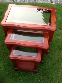 Nest of three dark wood glass top tables