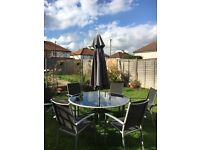 Garden dining table and chairs with parasol