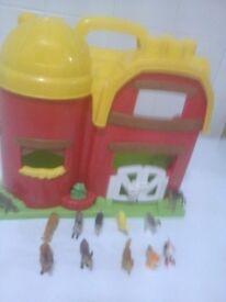 child's plastic toy barn with plastic animals