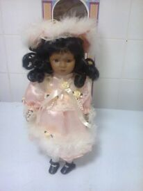 porcelain brown doll 13 inch high on a stand in a box