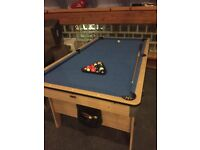 6ft x 3ft pool table in used condition with pool cue, also has table tennis cover and 2 bats