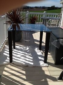 Smoked glass dining table with leather type legs £30.00