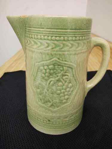 McCoy? stoneware pitcher with grape shield design, green muted/cream.
