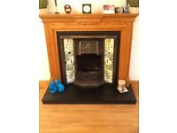 Fireplace in solid pine, feature side panels and cast iron inlay.