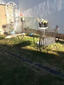 Metal crescent shape garden benches and small table