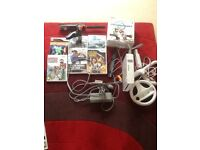 Wii console and games including steering wheel, nunchuck and fishing rod