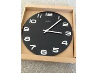 Black faced battery operated wall clock. Black clock with silver numerals.