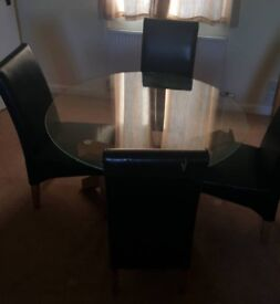 Glass top dining table with 4 high back chairs.