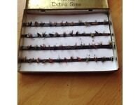 50 fishing flies in a metal tin held by magnetic strips.