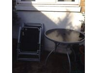 USED - Glass table and four deck chairs.