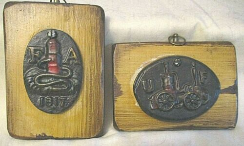 TWO WOODEN PLAQUES WITH CAST IRON FIRE DEPARTMENT SYMBOLS