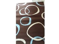 Brown rug with blue and cream circles