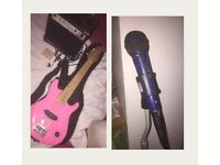 Pink eletric guitar with amplifier,guitar pics and mic with mic stand.